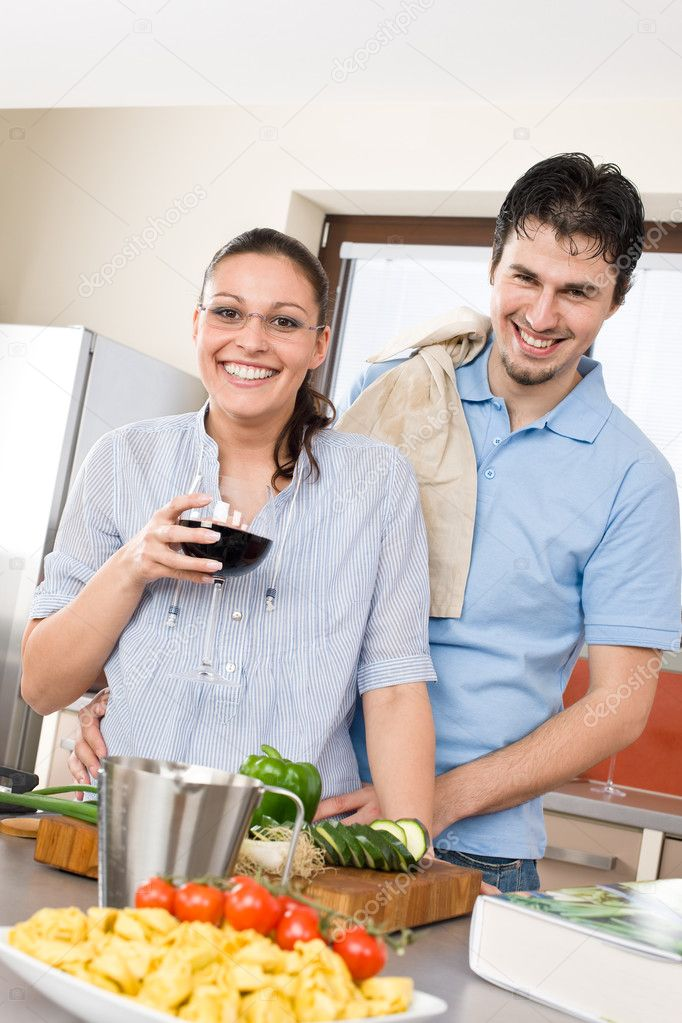 Cheerful couple in modern kitchen cook together, drink red wine — Stock Photo #4683550