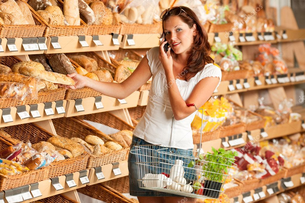 Grocery store: Young woman holding mobile phone and shopping basket — Stock Photo #4684193