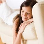 Smiling woman lying down on sofa — Stock Photo #4690440