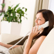On the phone home: Young woman calling in lounge — Stock Photo #4690483
