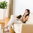 On the phone home: Young woman calling in lounge — Stock Photo #4690491