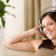 Stock Photo: Woman with headphones listen to music in lounge