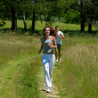 Young couple jogging outdoors in spring nature — Stok fotoğraf