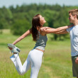 Young man and woman exercising in spring meadow — Stock Photo