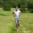 Young man with headphones jogging in a meadow — Stock Photo