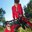 Young couple with mountine bike in spring nature — Stock Photo
