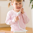 Smiling little girl on phone in lounge — Stock Photo