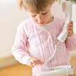 Little girl dial number on phone in lounge — Stock Photo