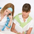 Student at home - two young woman study together - Stock Photo