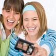 Stock Photo: Two young cheerful womtaking picture