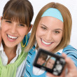 Stock Photo: Two young happy womtaking picture