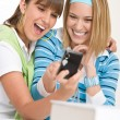 Two young cheerful woman with camera — Stock Photo