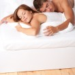 Young man and woman lying down in white bed — Stock Photo #4691039