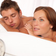 Young couple lying in white bed with alarm clock — Stock Photo #4691083