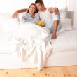 Young man and woman lying down in white bed — Stock Photo