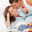 Young couple having home made breakfast in bed — Foto Stock