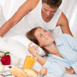 Happy man and woman having breakfast in bed together - Foto Stock