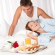 Young couple having luxury breakfast in hotel room - Stock Photo