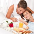 Happy man and woman having breakfast in bed together — 图库照片