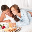 Happy man and woman having breakfast in bed together — Stock Photo
