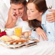 Happy man and woman having breakfast in bed together — Stock Photo #4691190