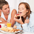 Happy man and woman having breakfast in bed together — Stock Photo #4691194