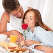 Happy man and woman having breakfast in bed together — Stock Photo #4691207