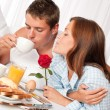 Happy man and woman having breakfast in bed together - 图库照片