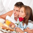 Happy man and woman having breakfast in bed together — Stock Photo #4691220