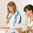 Student at home - two woman with book and laptop - Stock Photo