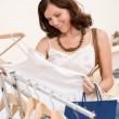 Foto de Stock  : Fashion shopping - Happy young woman choose clothes