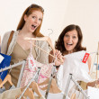 Fashion shopping - Two Happy woman choose sale clothes - Stockfoto