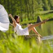 Stock Photo: Happy romantic woman sitting by lake splashing water