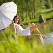 Happy romantic woman sitting by lake splashing water — Stock Photo