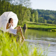 Happy romantic woman sitting by lake with parasol — Photo
