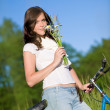 Stock Photo: Womwith old-fashioned bike and summer flower