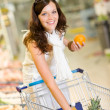 Grocery store - smiling woman shopping choose fruit — Stock Photo