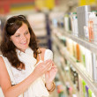 Shopping cosmetics- smiling woman holding shampoo — Stock Photo