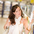 Shopping cosmetics - thoughtful woman choose shampoo — Stock Photo