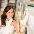 Shopping cosmetics - smiling woman choose shampoo - Stock Photo