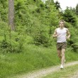 Young man jogging in nature — Stock Photo