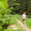 Sportive man jogging in nature by lake — Stok fotoğraf
