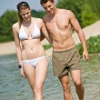 Happy couple in swimwear walk in lake — Photo