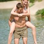 Piggyback - happy couple enjoy sun at lake — Stock Photo