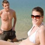 Couple on beach - woman in bikini sunbathing — Stock Photo