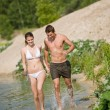 Couple in swimwear jogging at lakeside — Stock Photo