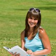 Smiling young woman read book in park — Stock Photo #4692089