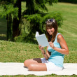 Smiling young woman read book in park — Stock Photo #4692091