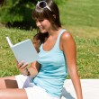 Smiling young woman read book in park — Stock Photo