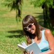 Happy young woman with book in park — Stock Photo